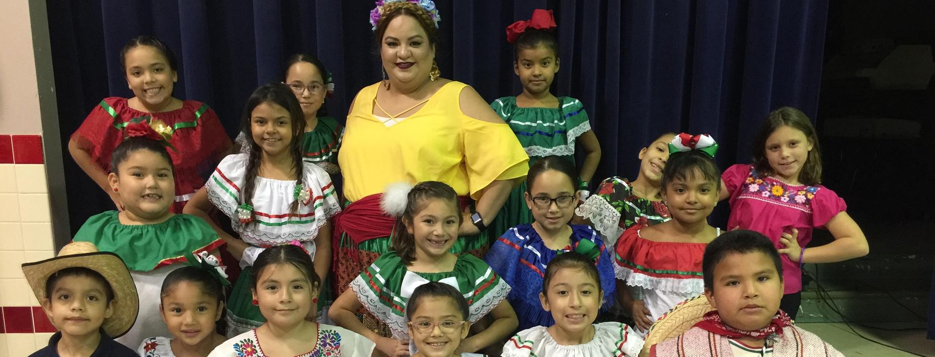 Group of students and Ms. Magadaleno in traditional Mexican clothes for dieciseis de septiembre