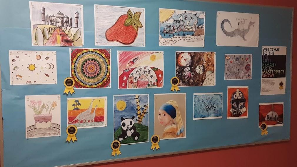A board displaying district art show selections from last school year, grades K through 5