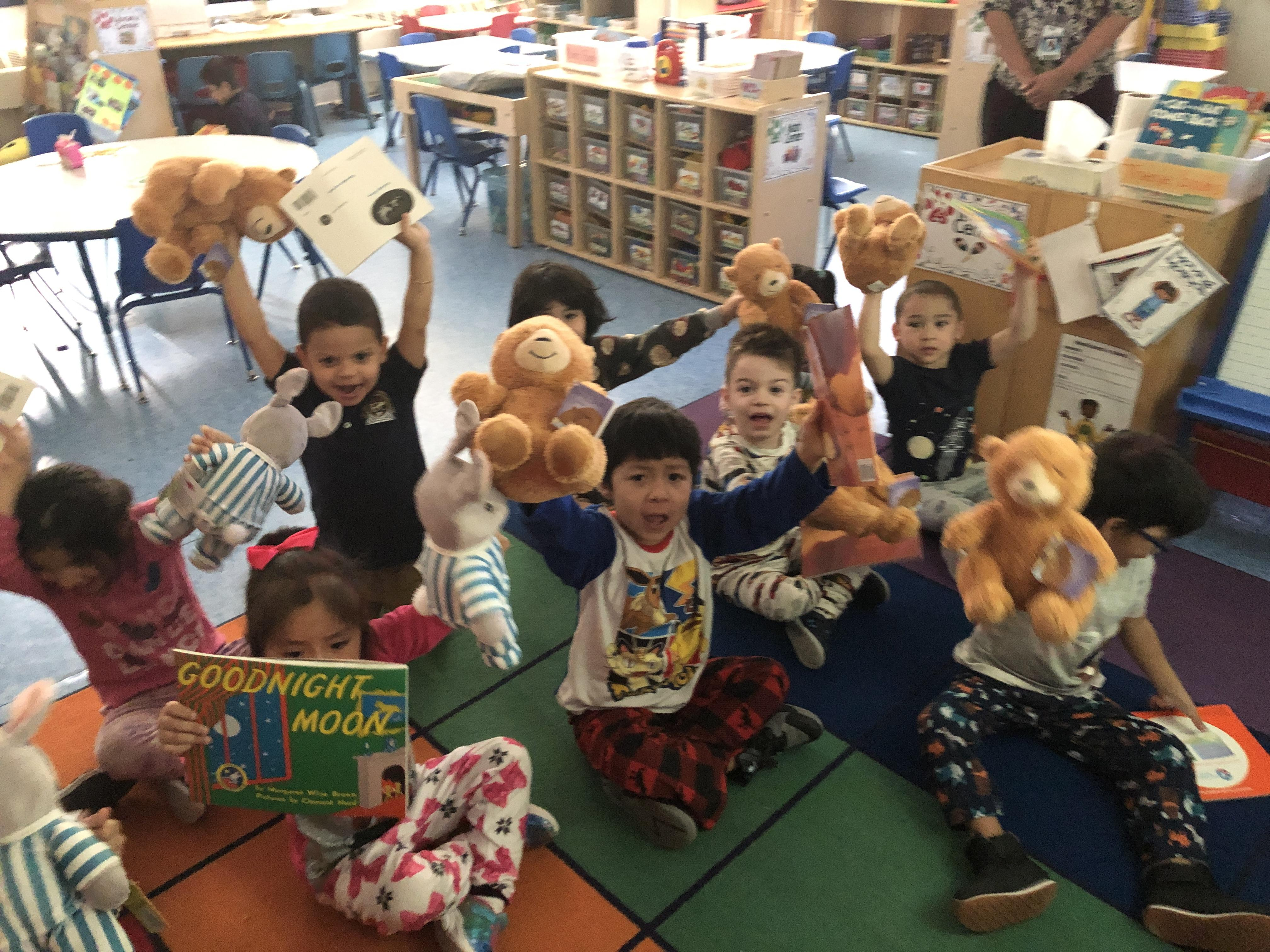 kids wearing pj's sitting on the class rug happily holding up their books and stuffed animals friends