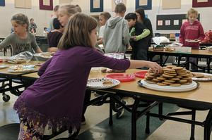 A Dix Street student reaches for a cookie to add to her plate.