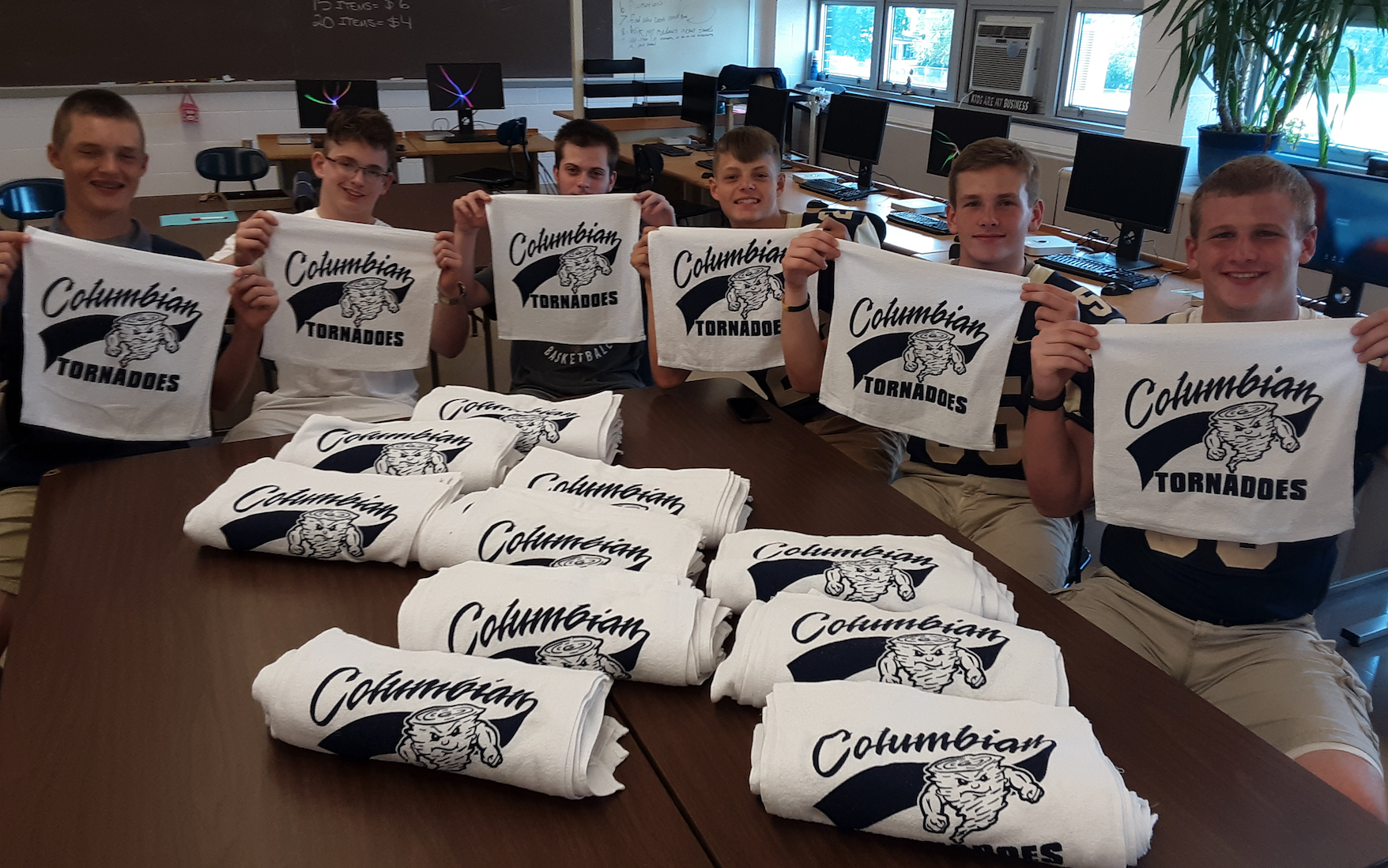 Image of the students displaying their white rally towels in their classroom.