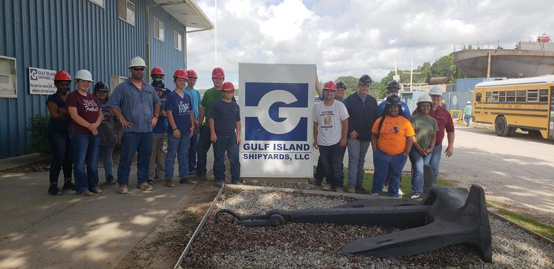 Students are standing next to the Gulf Island Shipyard sign