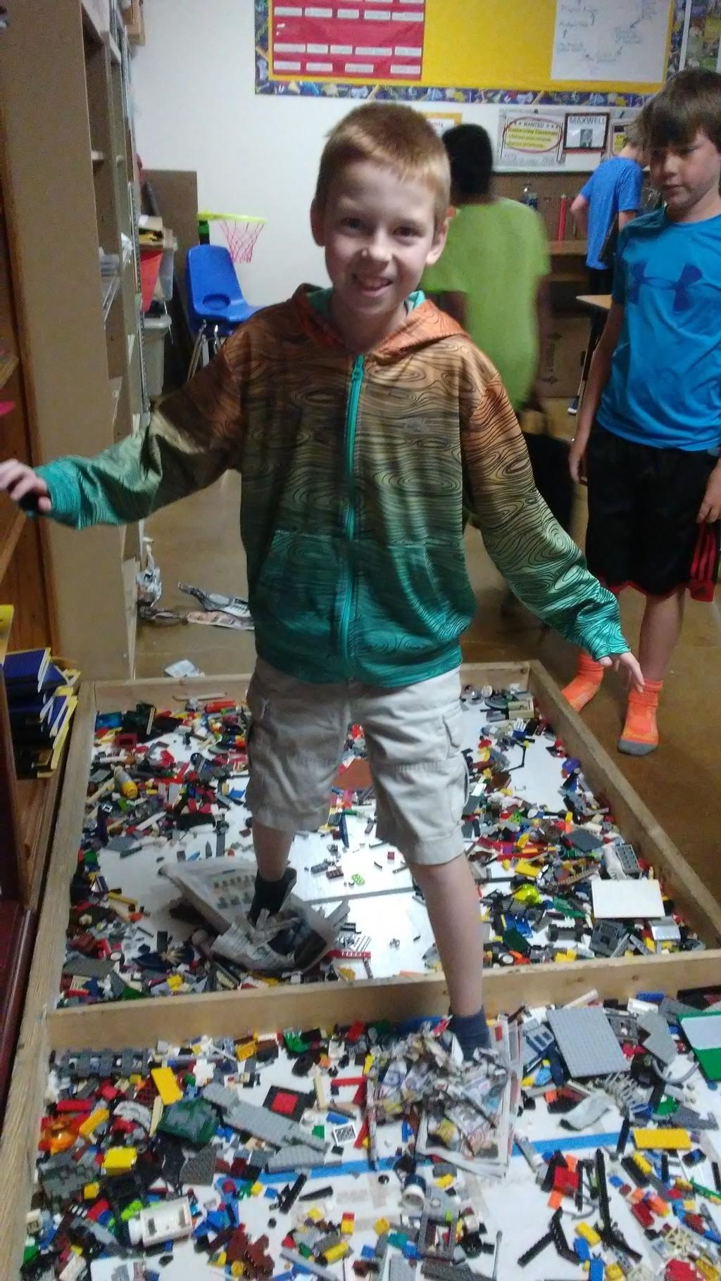 Fifth graders engineer newspaper shoes to protect their feet on a bed of legos.