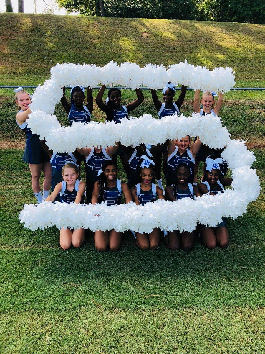 A group of cheerleaders making the letter S with poms.