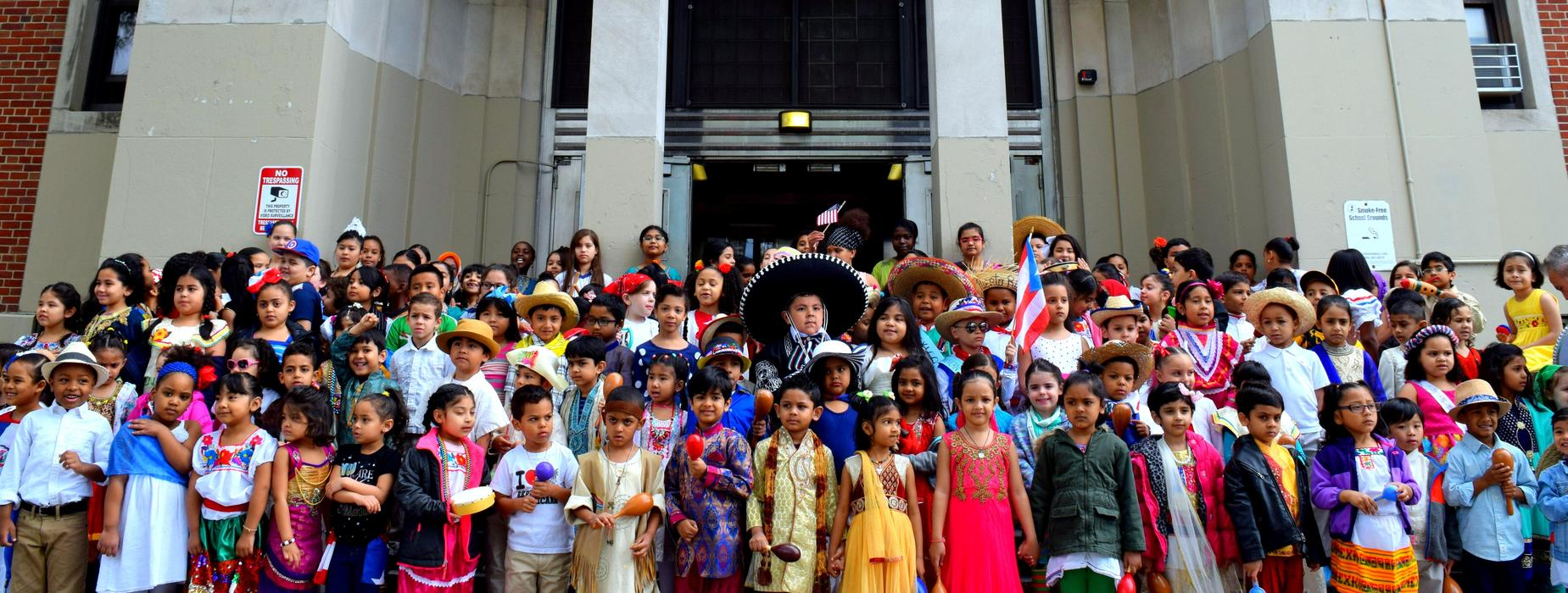 Students from PS8 stand in front of the school entrance dressed in multicolored and brilliant clothing representing their country of origin during the PS8 2019 Multicultural Week Parade.