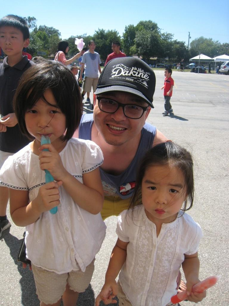 Families enjoy otter pops on this warm day.