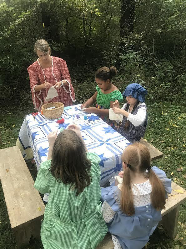 Studens in Pioneer clothing sitting at picnic table with sewing supplies.