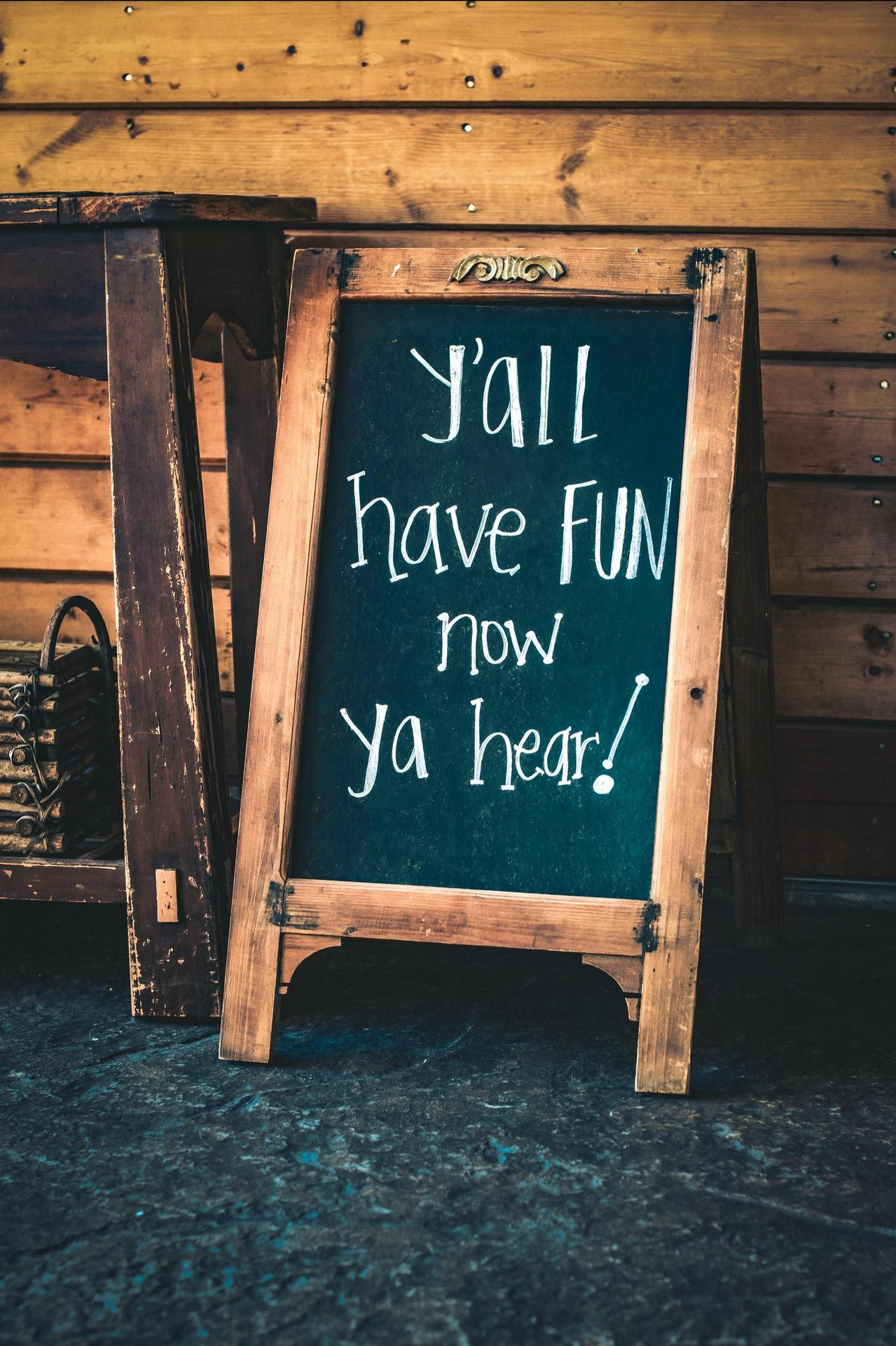 """Chalkboard with the message """"Y'all have fun now, ya hear!"""". By Tim Mossholder, via unsplash.com"""