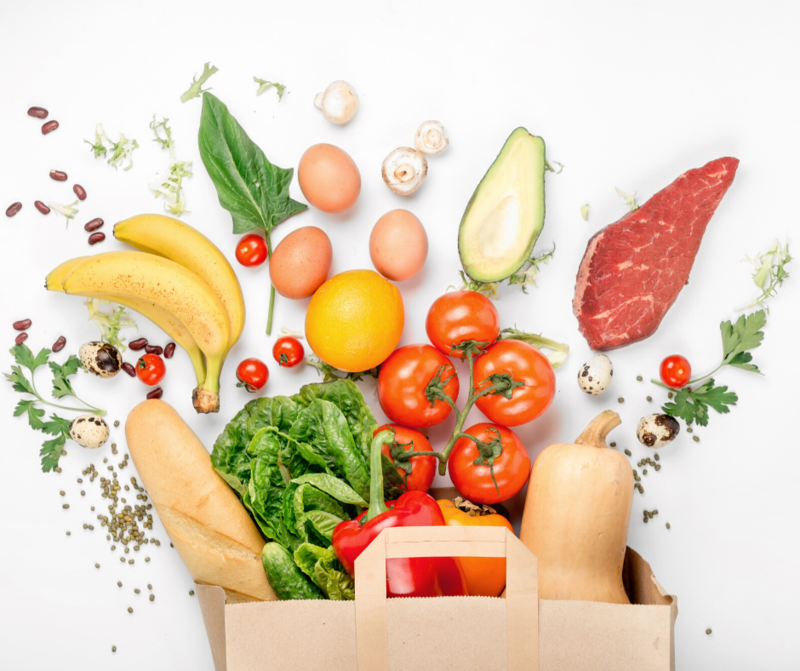 White Background, Brown paper bag full of grocery items: Bananas, bread, tomatoes, squash, steak, greens, eggs and beans