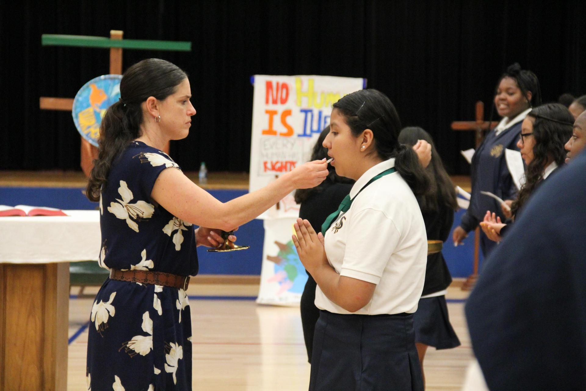 student receiving communion at school mas