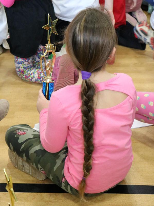 Photo of student holding trophy as her class wins award at annual Reading Marathon celebration.