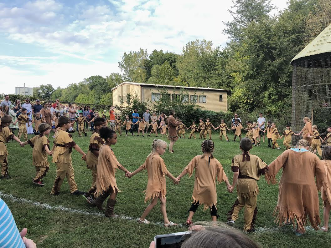 Students dressed in Native American clothing playing a circle game.