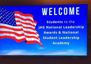 a graphic of a flyer announcement of the JAG National Conference.. white lettering with blue sky background and an American flag