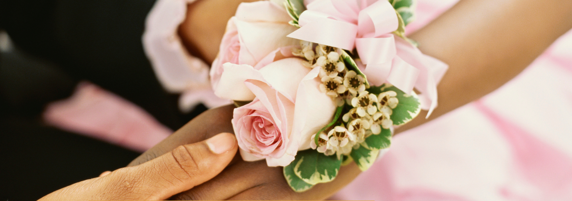 boy an girl hands together with a pink wrist corsage