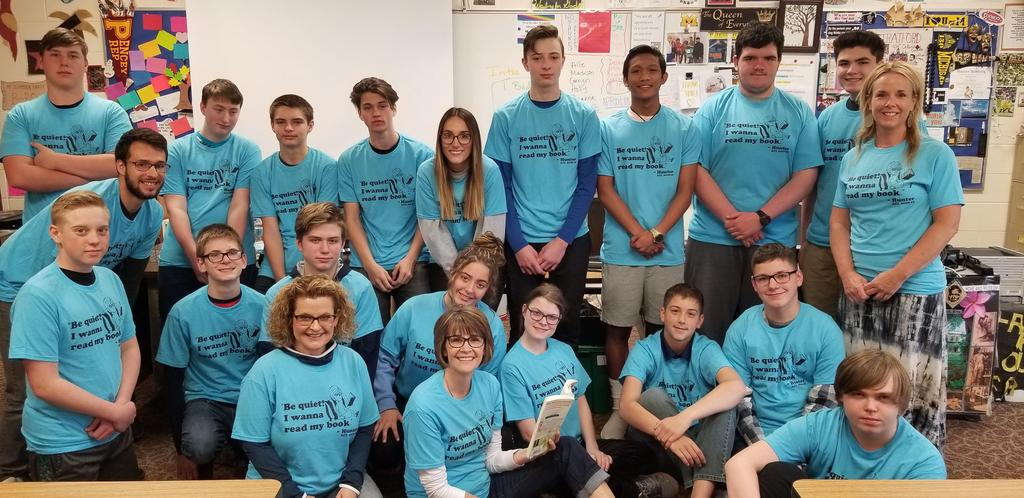 """Class of students wearing matching t-shirts that say, """"Be quiet!  I want to read my book."""""""