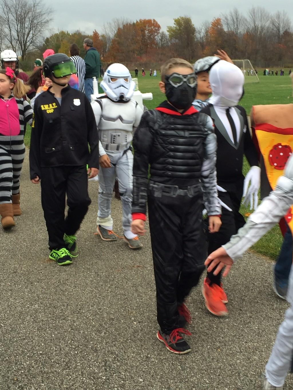 kids in costume parade outside around playground