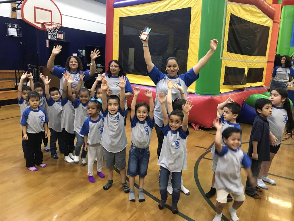 teacher, aide and students with hands up showing their excitement to take turn in bouncy house