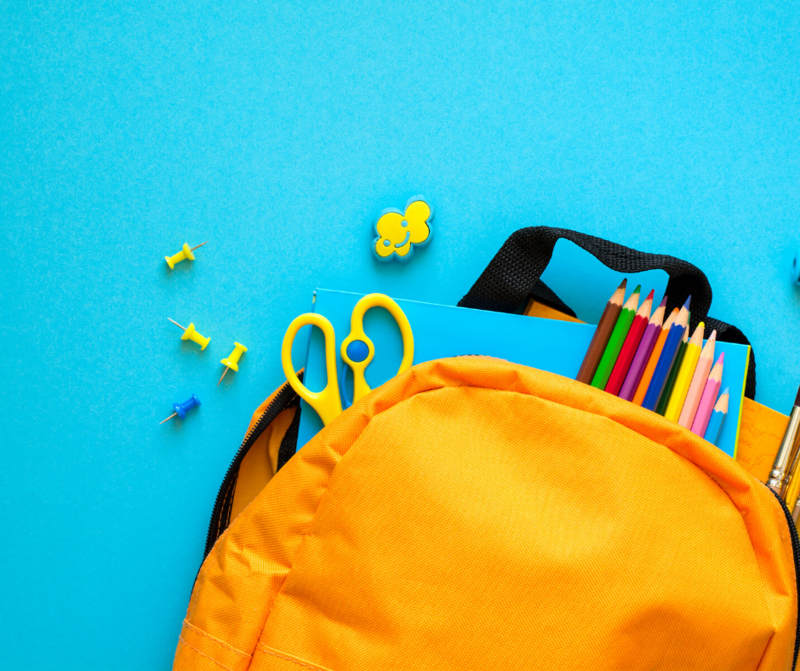 Blue background, yellow backpack in the right corner, school supplies are scattered throughout.