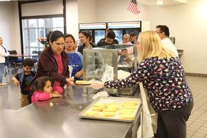 Staff member serving dinner to a family
