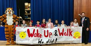 Tamaques principal David Duelks, mascot Tammi the Tiger and students hold banner on Walk to School Day.