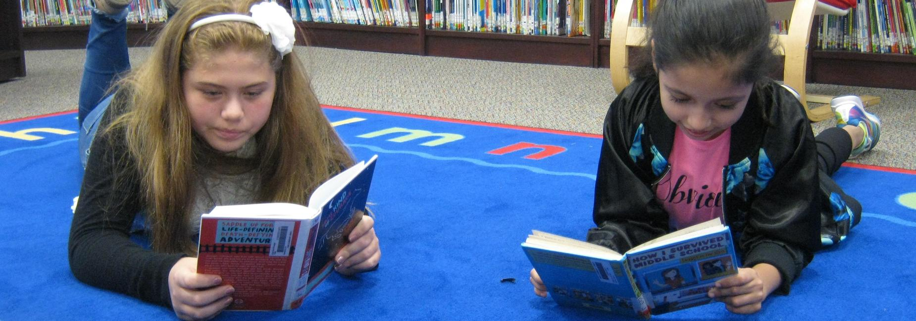 Students lay on the library carpet and read.