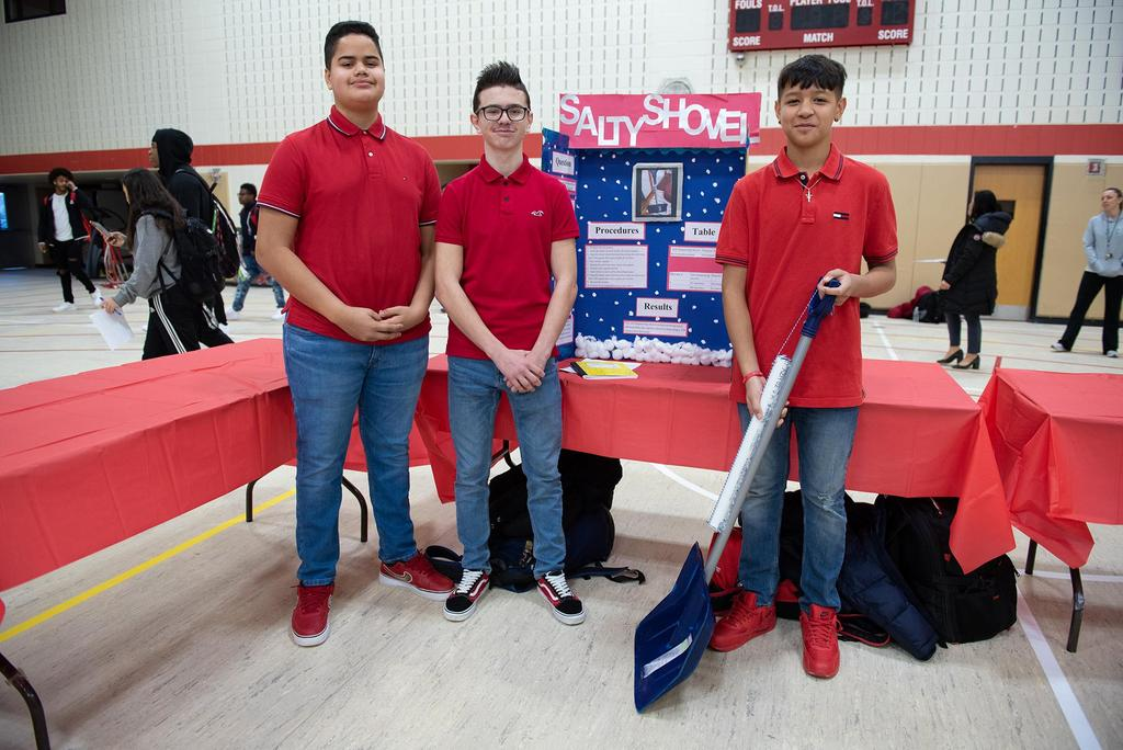 Three students stand in front of their project, Salty Shovel, a prototype for a shovel that also spreads salt