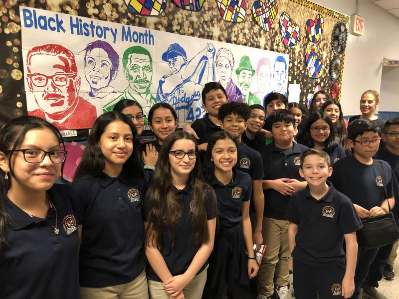 Mrs. Colangelo and her class with the Black history month mural