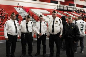 picture of five veterans in uniform with tie standing in line.