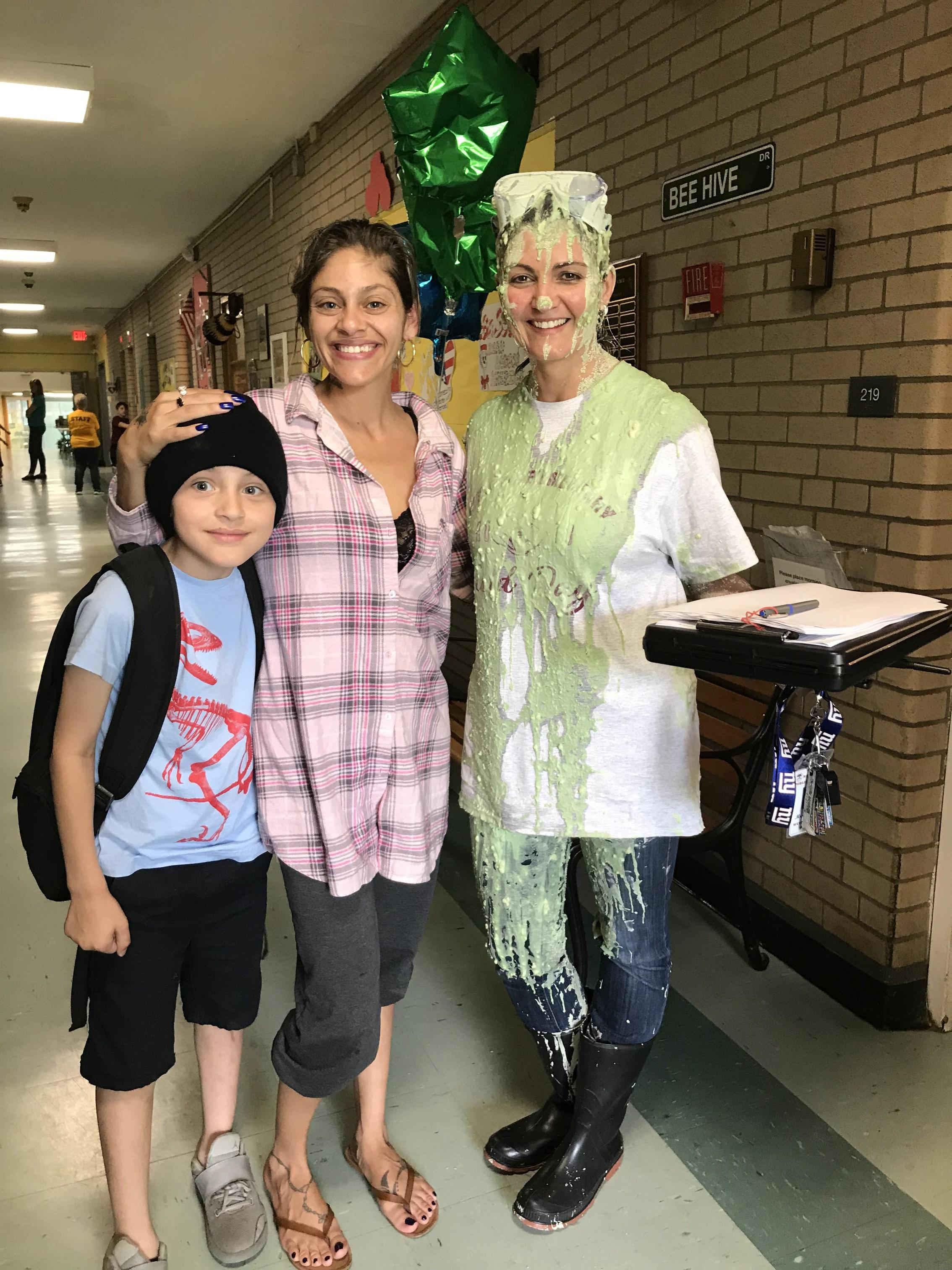 Mrs. Fioretti smiles for the camera with a student and his mom.
