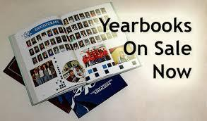 picture of a open yearbook with the wording yearbook on sale now