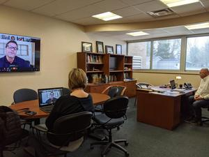 Mrs. Koenig and Supt. Haase watch the announcement from his office
