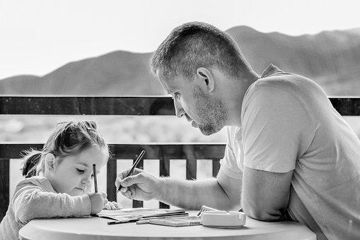 Father helping his daughter with homework.