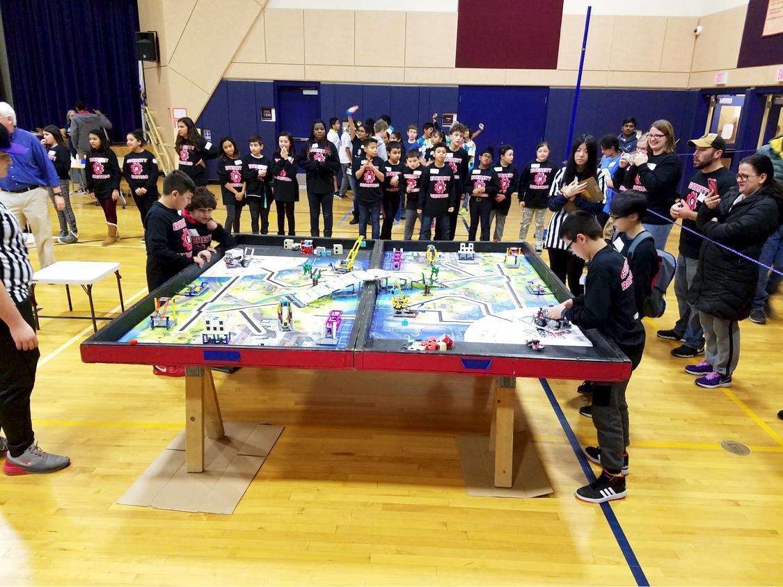 Everett students are shown on opposite ends of a large track laid across a table