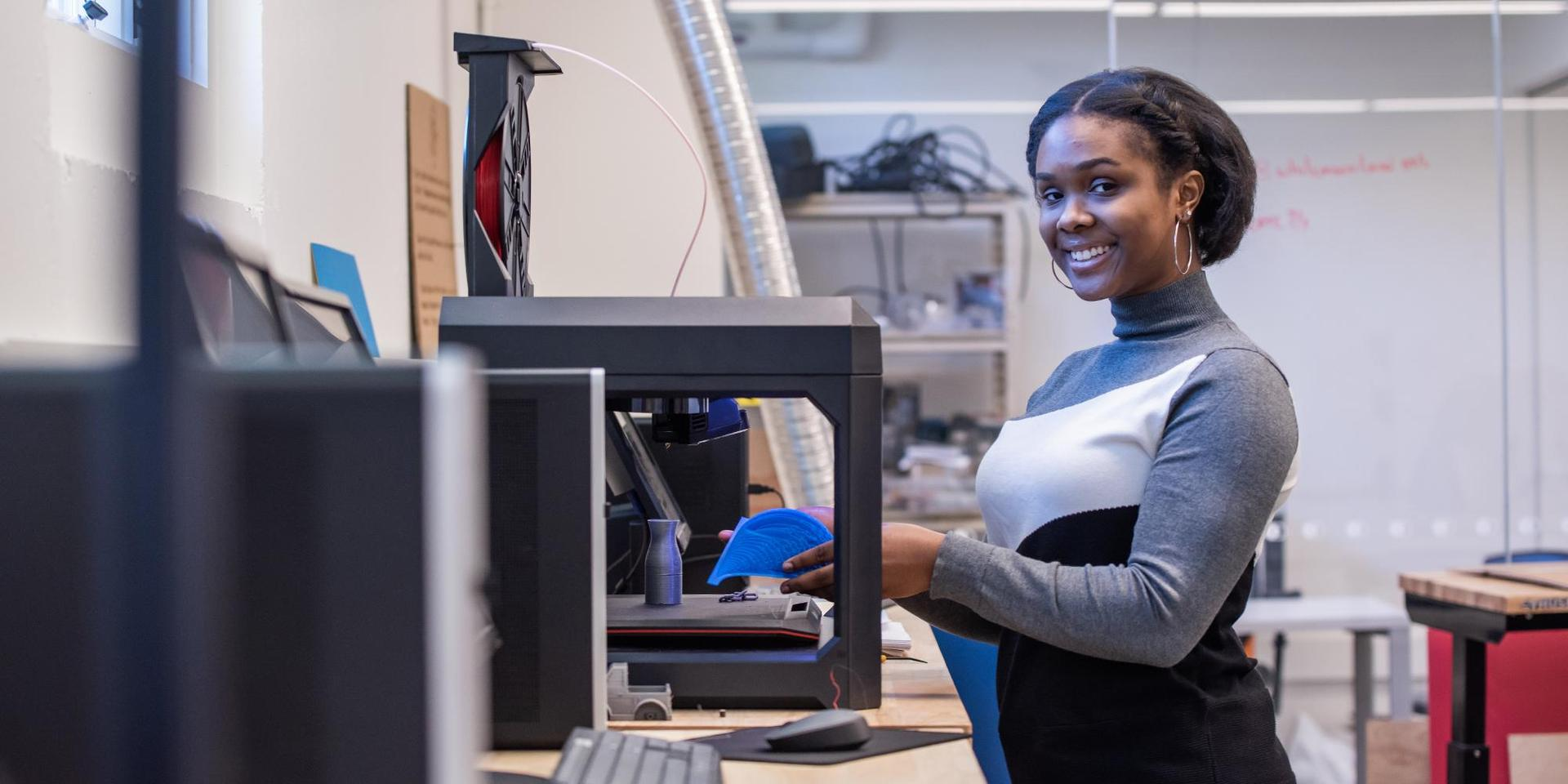 A student using a 3D printer in the I^3 Lab.