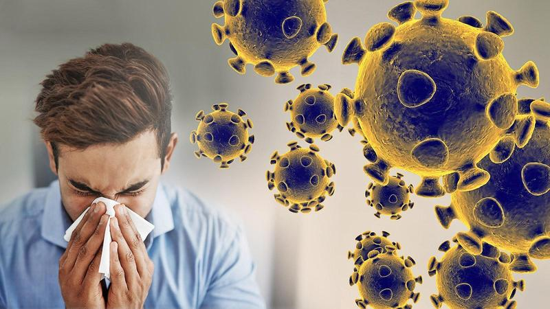 Image of man blowing his nose with image of coronavirus in the background
