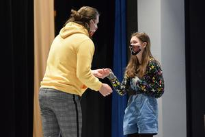 girl and boy talking on stage