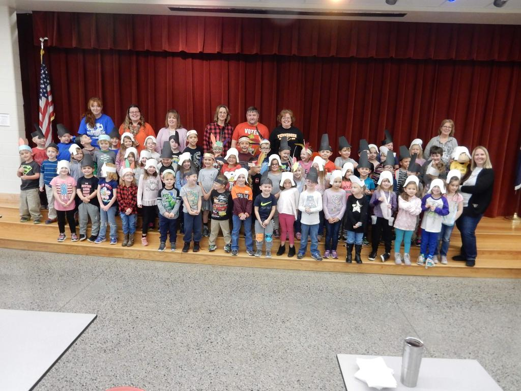 Kindergarten students dressed as Pilgrims and Native Americans standing on the stage for a group photo.