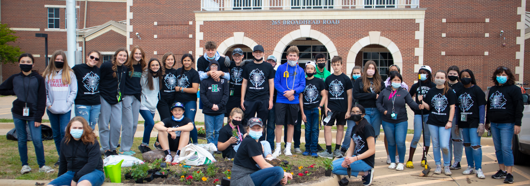 large group of teens outside of campus after planting spring flowers