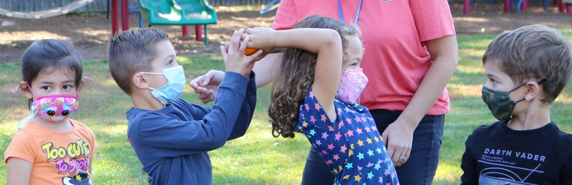Photo of students passing small pumpkin as part of annual Pumpkin Patch festivities.
