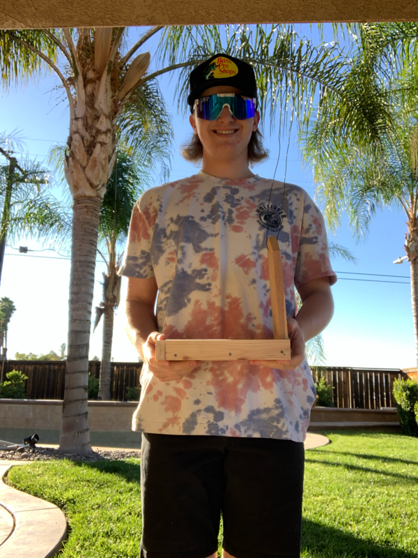 Student holding his bird feeder project he created in class