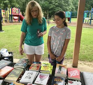 Busbee teacher Lisa Fisher helps Kaitlin Metz look for her next summer read at Wednesday's event.
