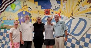 Celebrating the changes to the Media Center are, l-r: Media Center Coordinator, Meghan Crowther; Originating Artist, Sonny Harlow; K-2 Team Leader, Margaret Daniel; local artist, Megan Davies; and Head of School, Peter York.
