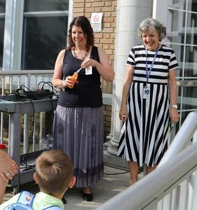 Photo of Lincoln School principal and staffer welcoming students on first day of school.
