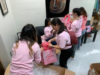 students opening boxes with the pink bags