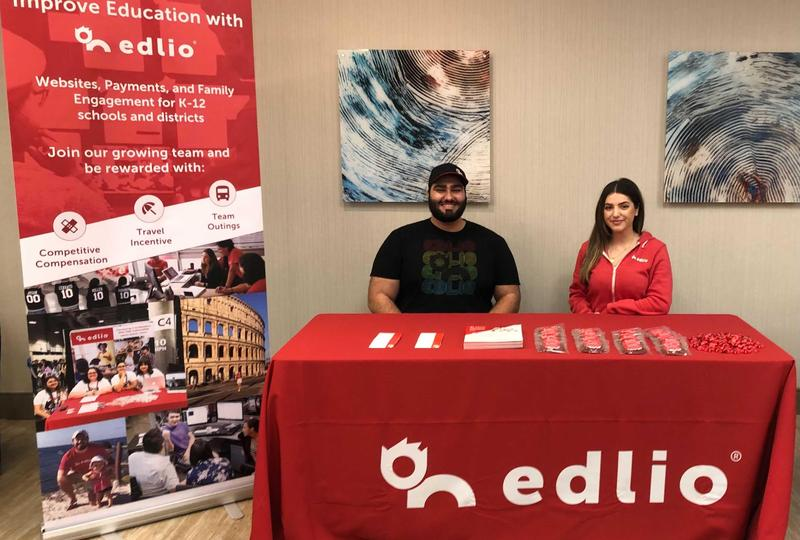 An Edlio conference booth with two employees sitting at the table.