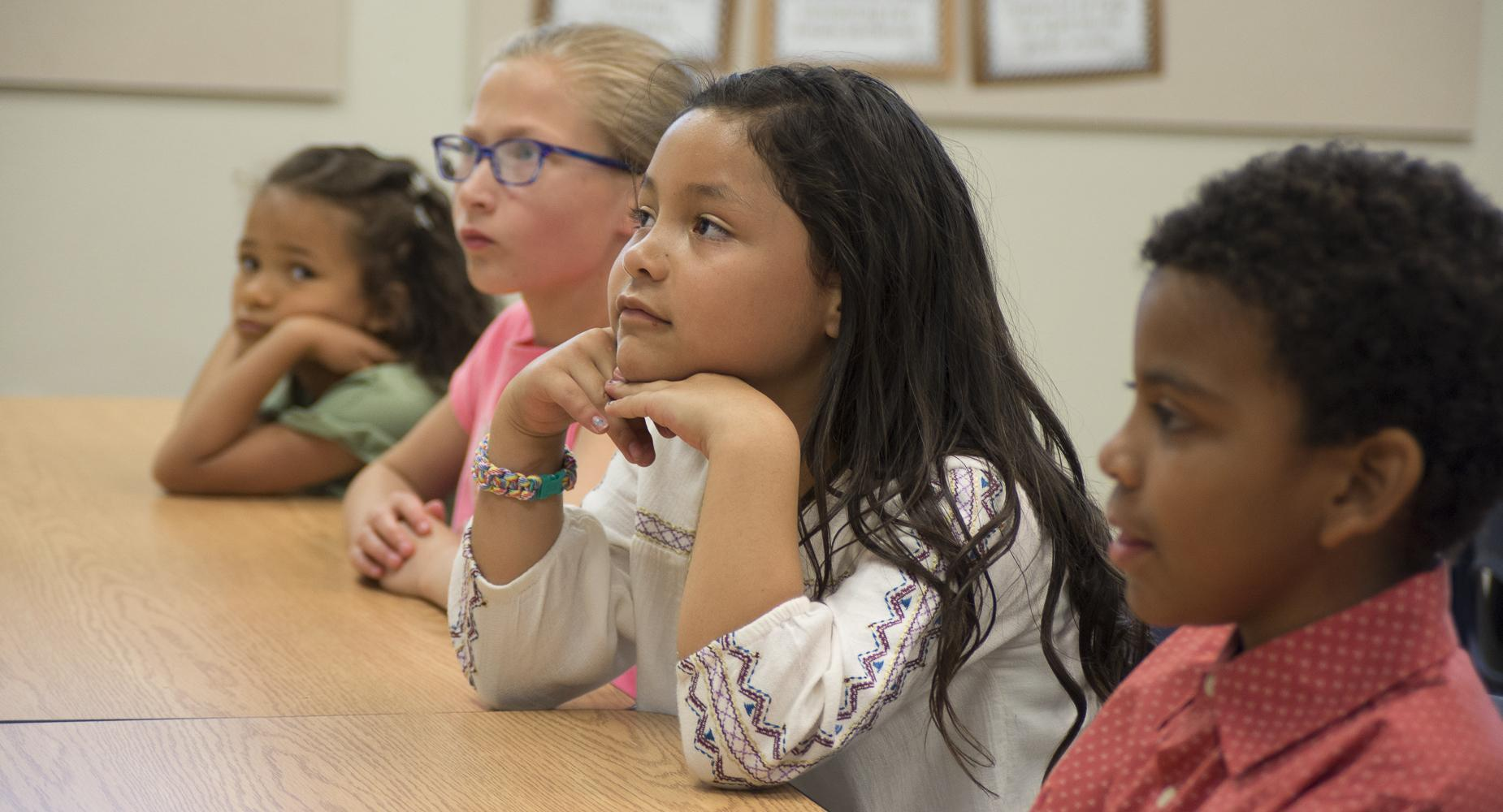 Girl rests her chin on her hands while listening in class.