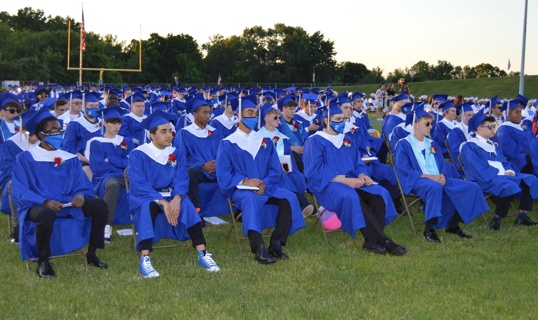 BHS Senior boys sitting in their royal blue cap and gowns listening to the Class Officers speeches