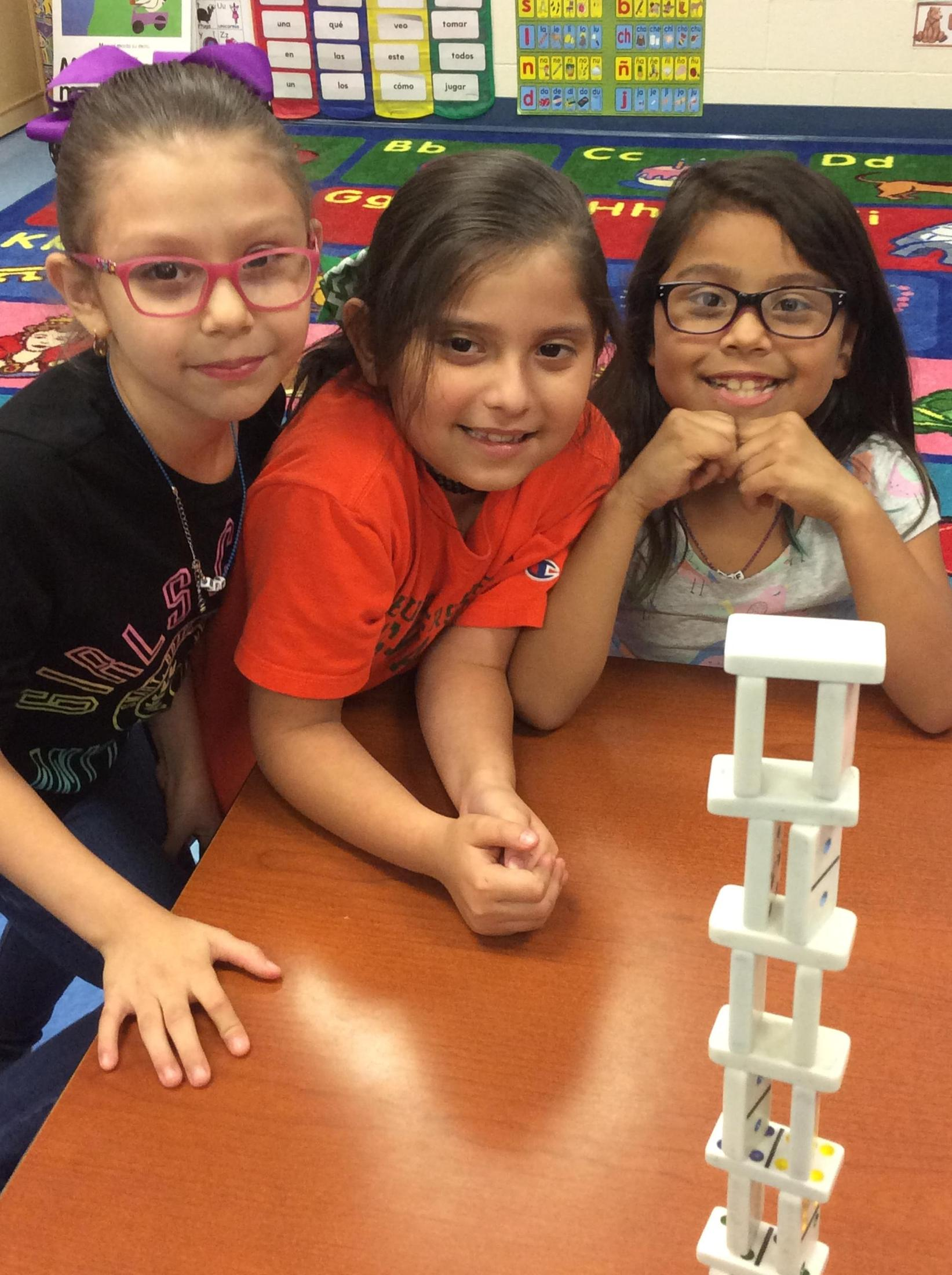 Students stacking dominos
