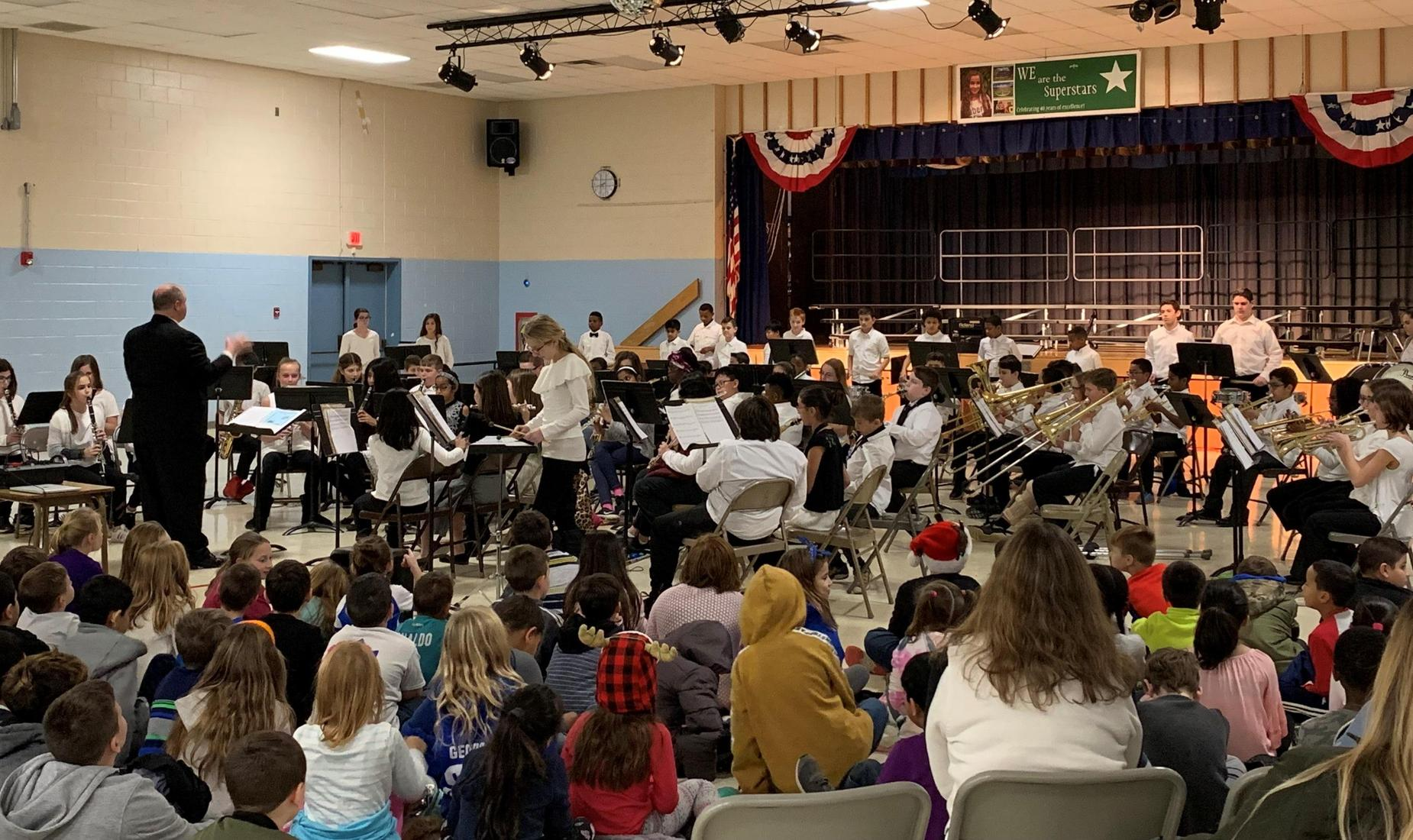 Elementary Band performs their winter/holiday concert for their classmates. Boys and girls are dress in white tops and black pants.