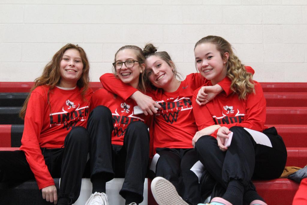 Four girls sitting on bleachers